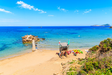 Fototapete - Lifeguard tower and colourful kayaks on sandy Es Figueral beach, Ibiza island, Spain