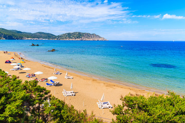 Fototapete - View of sandy Es Figueral beach with sunbeds and umbrellas, Ibiza island, Spain