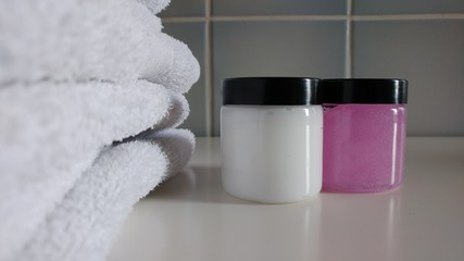 White Towels and Cosmetic products in tiled Bathroom