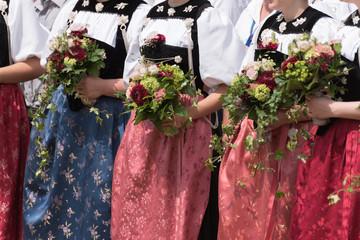 drei Frauen in schweizer Tracht mit Blumenstrauss