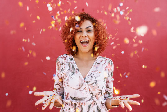 Happy young woman celebrating with confetti all around.