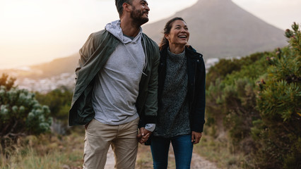 Smiling couple walk through country trail