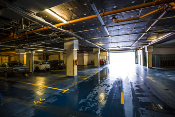 Empty places in colorful underground garage, wet floor and incoming sunlight