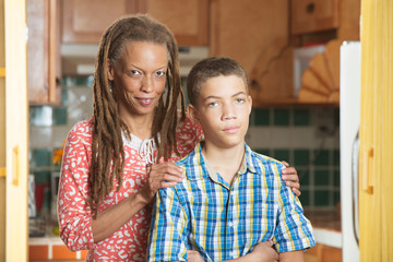 Mother stands with her teen son with one hand on either shoulder