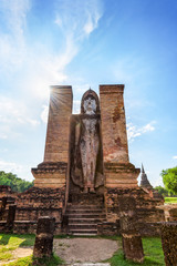 Ancient Buddha statue stand posture under the blue sky among the ruins of Wat Maha That temple at Sukhothai Historical Park is an old city and famous attractions, Sukhothai Province, Thailand