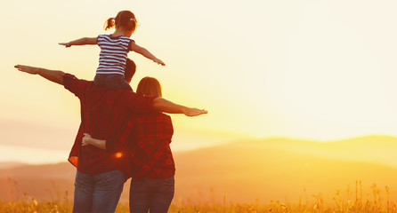 Happy family: mother father and child daughter on sunset Wall mural