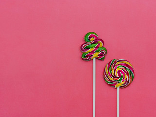 Lollipop Flat lay Minimal concept Two colorful lollipops on a pink background Round lollipop and a spiral lollipop