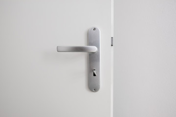metal door handle with key on white door Wall mural
