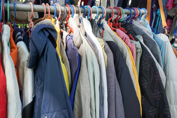 Various kind of used clothes on display for sale at thrift or bundle shops in market for cheap clothes.