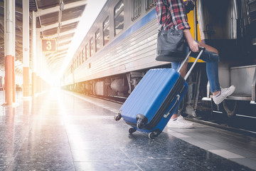 Alone traveler wait suitcases waiting for her train on platform of railway train station in summer. Alone travel concept. Wall mural