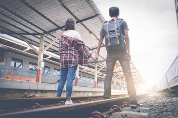 Enjoying travel. Two young man and woman traveling at railway train platform with sunny. travel summer concept. vintage filter.