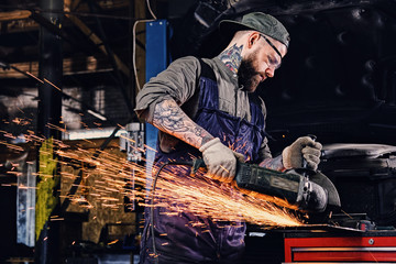 Mechanic cuts steel car part with an angle grinder.