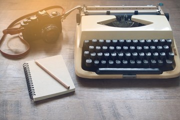 Old vintage typewriter, film camera and blank notebook on rustic wooden table