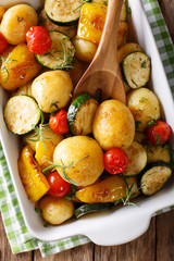 Vegan food: potatoes baked with zucchini, pepper and tomatoes close-up in baking dish. vertical top view
