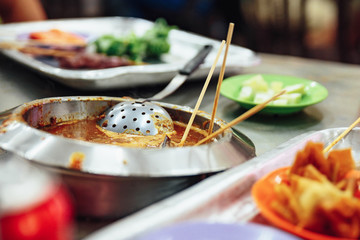 Warming satay sauce in the pot. Satay is a dish of skewered grilled meat with Javanese origins in Malacca City, Malacca, Malaysia.
