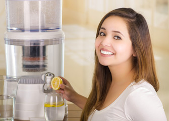 Beautiful smiling woman holding a cut lemon in her hand with a filter system of water purifier on a kitchen background
