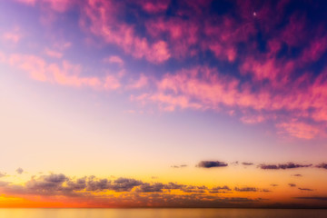 Colorful idyllic sunset over the sea near Hout Bay, Cape Town, South Africa in glowing pastel tones with a view over the sea towards the horizon, some fine clouds and the moon