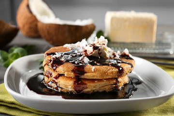 Tasty homemade coconut pancakes with chocolate sauce on plate