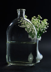 A bottle of water and and lilies of the valley in a vase