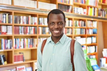 Portrait of dark-skinned male student holding rucksack standing in library choosing interesting book to read having pleasant smile enjoying reading. African student standing against bookshelves