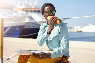 Fashionable dark-skinned man in cap, shirt and yellow trousers sitting in harbor eatting sandwich holding map having rest looking attentively aside noticing someone isolated over sea background