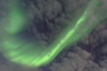 Polar lights, the aurora and the stars visible through the clouds.