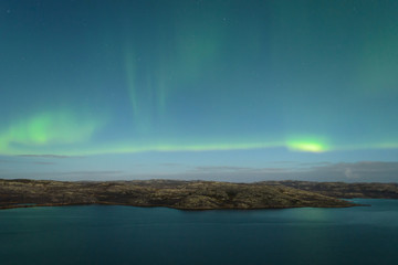 The Aurora in the sky above the hills and water on a moonlit night.