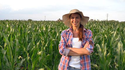 Beautiful girl (woman) farmer smiling, looking, checking corn fields, straw hat, greens background. Concept: ecology, corn, bio product, inspection, water, natural products, professional, environment.