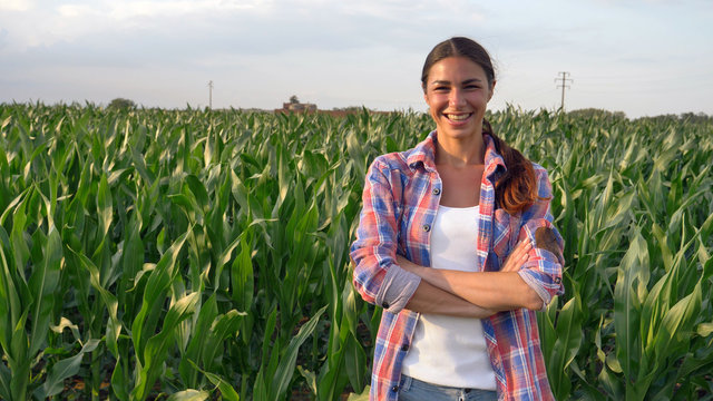 Beautiful girl (woman) farmer smiling, looking, checking cornfield, young tanned, green background. Concept: ecology, corn, bio product, inspection, water, natural products, professional, environment.