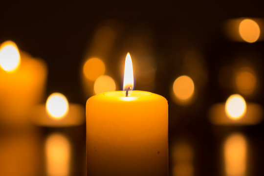 candle flame glowing in darkness