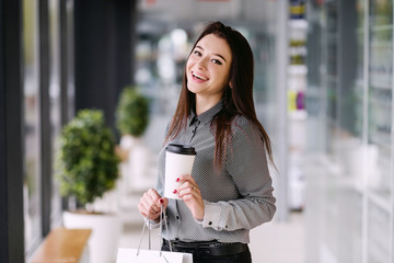 Brunette girl drinks a coffee from a large paper cup