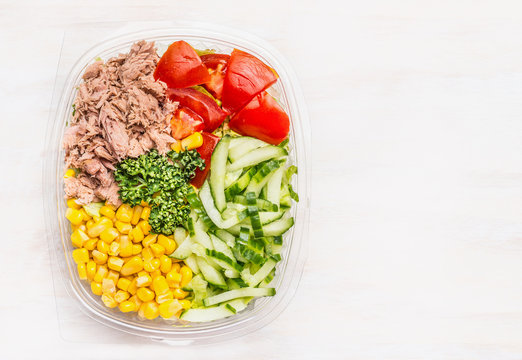 Fresh dieting salad in lunch box on white wooden background , top view