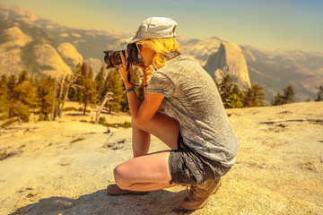 Travel photographer takes shot on top of Sentinel Dome, a granite dome in the south wall of Yosemite Valley. Woman summer mountain hiker in a summit overlook. Yosemite National Park, California, USA.