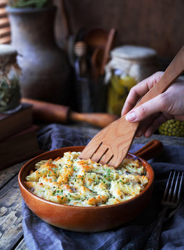Fusilli pasta casserole with chicken, cheese dor blu and spices served on a clay plate on a wooden kitchen table in rustic style. Close-up.
