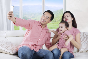 Two parents and daughter taking selfie photo