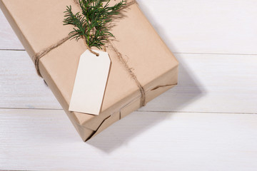 Kraft paper box and green leaves on woodean background.