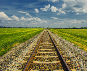Spoed Fotobehang Spoorlijn railroad track in open green field, summer time traveling, freedom of movement