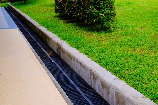 motorway and road - grass. Aqueduct between nature and city. iron grate of water drain in grass garden field. Steel rusty grating in the Grass garden and concrete