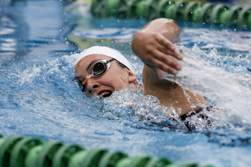 Chica practicando el deporte de la natación en piscina de verano estilo crol
