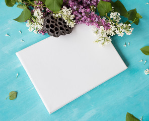 Mock up poster on a bright blue wooden table. White empty canvas and spring flowers.