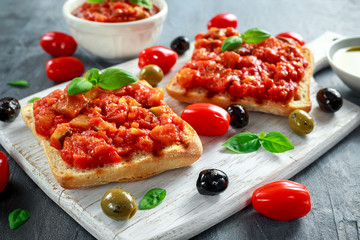 Fresh homemade crispy Italian appetizer Bruschetta topped with tomato, eggplant, Zucchini, Yellow pepper, garlic and basil on white wooden board. healthy food
