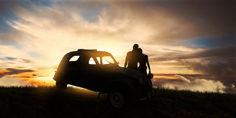 Couple embracing near the car at sunset