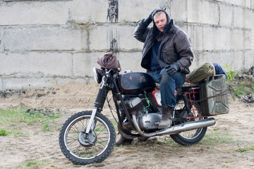 A post apocalyptic man on motorcycle near the destroyed building