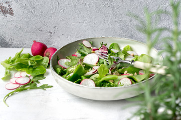 Radish salad on white concrete table. Healthy mix from fresh ripe vegetables, lettuce mix and olive oil.