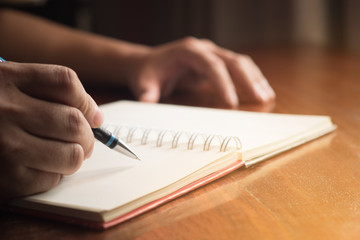 Man hand with pen writing on notebook.