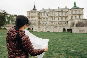 Happy girl traveler on vacation with map of landmarks, verlooking the ancient castle