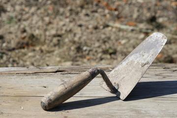 trowel on wood floor, side view