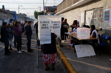 A woman prepares her ballot as other people wait to cast their votes for governor of the State of Mexico at a polling station in Nezahualcoyotl