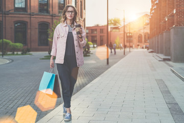 Young woman in glasses is walking along city street,carrying shopping bags and holding cup of coffee.