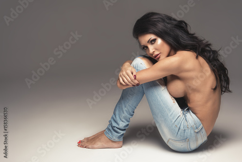 47ecdd28569 Sexy attractive brunette woman posing only in jeans in studio